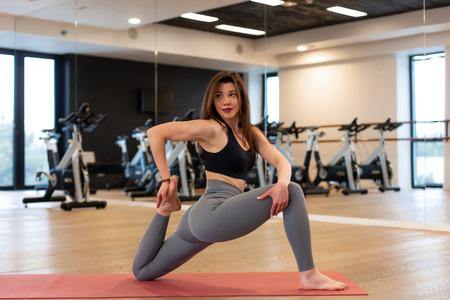 Foto de Young sexy woman doing stretching exercises in gym. - Imagen libre de derechos