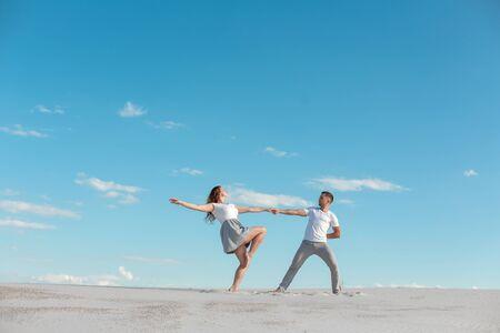 Photo pour Romantic couple dancing in sand desert at blue sky background. - image libre de droit