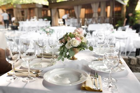 Photo pour Wedding table setting decorated with fresh flowers in a brass vase. Wedding floristry. Banquet table for guests outdoors with a view of green nature. Bouquet with roses, eustoma and eucalyptus leaves. - image libre de droit