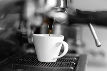 Photo pour A coffee machine pours freshly brewed hot coffee into a white cup. - image libre de droit