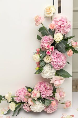 Photo for Wedding decorations. Holiday decoration vase with fresh flowers near the wedding arch. Pink roses and carnations. - Royalty Free Image