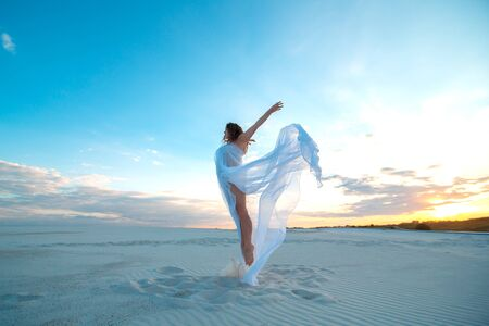 Photo pour A girl in a fly white dress dances and poses in the sand desert at sunset. - image libre de droit