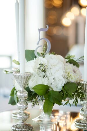 Foto für Wedding table setting is decorated with fresh flowers and white candles. Wedding floristry. Bouquet with roses, hydrangea and eustoma. On the background blur are burning garlands with light bulbs. - Lizenzfreies Bild