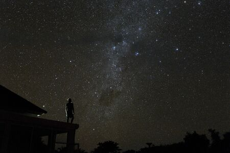 Photo for alone woman on rooftop watching mliky way and stars in the night sky on Bali island - Royalty Free Image