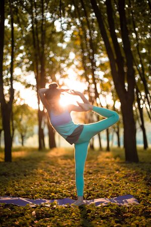 A young sports girl practices yoga in a quiet green forest in autumn at sunset, in a yoga asana pose. Meditation and oneness with nature.