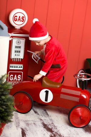 Photo pour Little boy in santa costume rides a toy red car. Happy childhood. Christmas Eve - image libre de droit