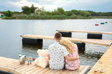 Photo pour Romantic date surprise. A young guy and a girl on a wooden pier. Hug and kiss while sitting on the pier. Romantic love story. - image libre de droit