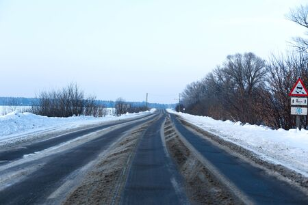 Winter poorly cleared road. Road in the countryside strewn with snow. Snowdrifts.