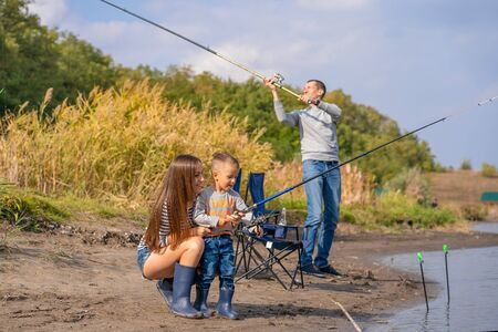 Photo pour A happy family spends time together they teach their son to fish - image libre de droit