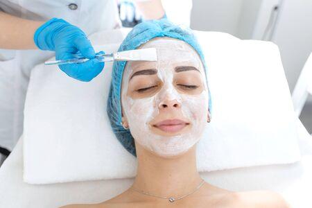 Photo pour Woman professional doctor beautician applies a mask on a patient's face for skin care. Cosmetic procedures for skin rejuvenation and nutrition. - image libre de droit