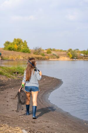 Photo pour A beautiful young girl goes fishing. A girl with a fishing rod and a cage in hand is walking along the lake. - image libre de droit
