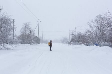 Photo pour A rustic man is walking down the street in winter with a yellow backpack. Snow blizzard. - image libre de droit