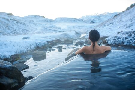Photo for The girl bathes in a hot spring in the open air with a gorgeous view of the snowy mountains. Incredible iceland in winter. - Royalty Free Image
