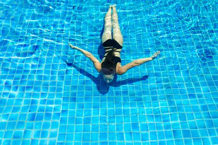 Photo pour Young sexy slim woman relaxing in swimming pool with crystal blue water. - image libre de droit
