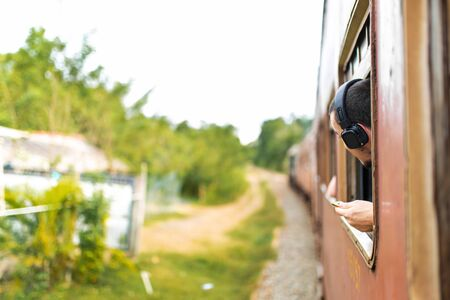 Photo for Train ride in Sri Lanka. The man in the headphones looks out the window. - Royalty Free Image