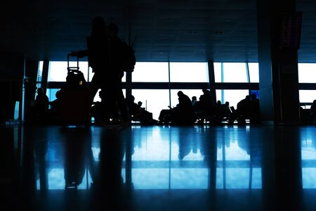 Photo pour Silhouettes of people walk in front of a large stained glass window. People at the airport walk along the corridor. - image libre de droit