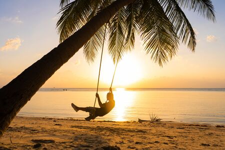 Photo pour The guy enjoys the sunset riding on a swing on the ptropical beach. Silhouettes of a guy on a swing hanging on a palm tree, watching the sunset in the water - image libre de droit
