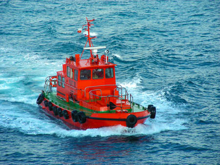 Photo pour Red ship tugboat sailing in the blue sea breaking the waves. - image libre de droit