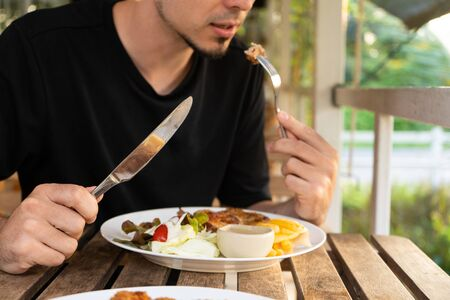 Photo pour Guy eating steak at a table in a summer cafe. - image libre de droit