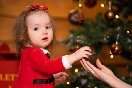 Photo pour Fabulous Christmas holidays mom and daughter in red dresses decorate the Christmas tree. Cozy family holiday. - image libre de droit