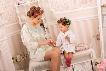 Photo pour Adorable little girl with her mother in curlers paint their fingernails. Copies mom's behavior. Mom teaches her daughter to take care of herself. Beauty day. - image libre de droit