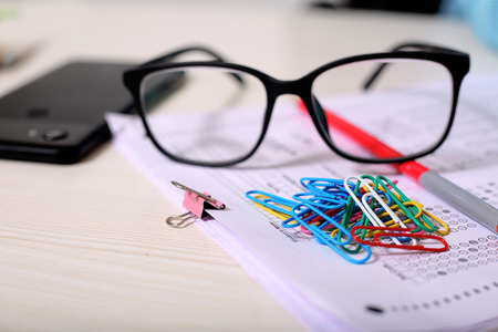 Photo pour Picture of OMR sheet, paper pin, glasses, pen and phone. Isolated on wooden background. - image libre de droit