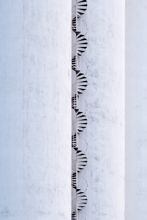 A tall spiral stair on the outside of a building