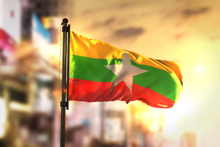 Foto de Myanmar Flag Against City Blurred Background At Sunrise Backlight - Imagen libre de derechos