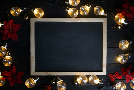 Photo pour Blackboard Between Light Bulbs and Red Poinsettia on Black Wood. Top View Copy Space - image libre de droit