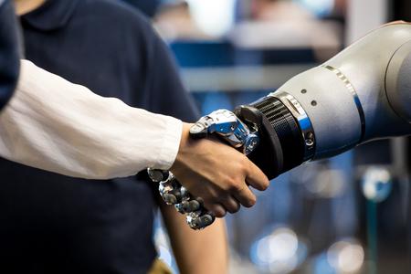 Photo pour Robot hand shaking human hand - image libre de droit