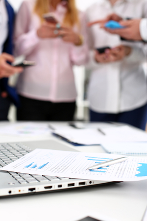 Important paper lie at table with group of colleagues in background closeup. Trade result, paperwork job, number balance, bank credit, loan money, invest payment, irs, commerce partnership concept