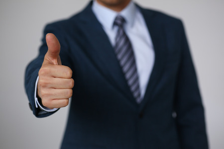 Male hand showing OK or confirm sign with thumb up during conference closeup. High level and quality product, serious offer, mediation solution, happy client, creative adviser participation concept