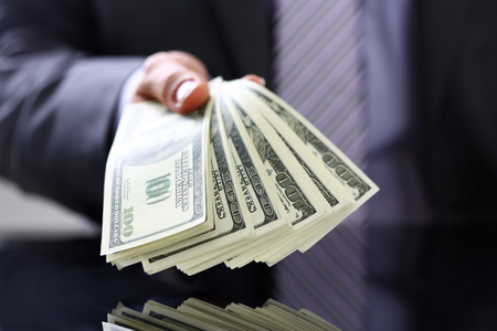 Man in suit and tie hold in arm pack of hundred dollar bills closeup. Stock market, exchange, earn pile, rich present, gift, employer prepayment, service gratitude concept