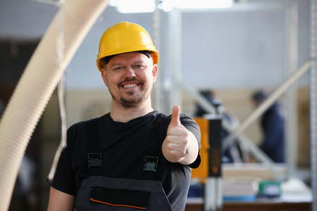 Smiling worker in yellow helmet show confirm sign