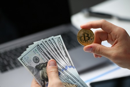 Foto de Male hand holds bitcoin and dollar coin on - Imagen libre de derechos