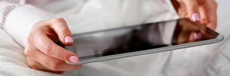 Photo pour female hand holds tablet in home setting while - image libre de droit