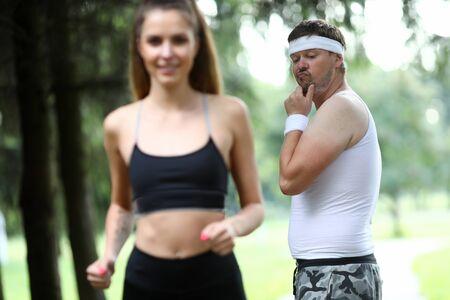 Photo pour Obese man doing morning jogging in park - image libre de droit