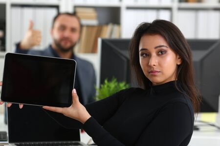 Photo pour young pretty brunette woman in office work with her boss hold tablet in hands - image libre de droit