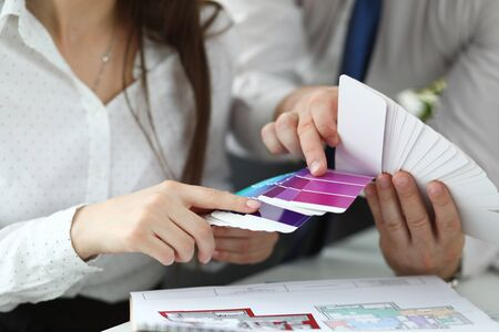 Foto de Focus on male and female hands holding colored palette. Trendy creator in white blouse pointing at suitable colour with tender hands to coworker. Art design concept - Imagen libre de derechos
