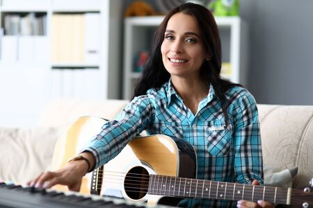 Portrait of wonderful female learning new musical composition. Beautiful woman accompanying on piano and guitar. Music and art concept. Blurred background