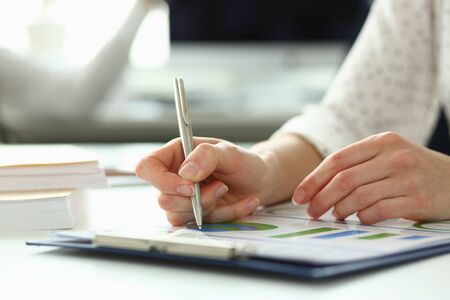 Photo pour Close-up of tender female arms writing something in paper folder with important contract that can highly increase income of corporation profit. Company meeting concept - image libre de droit