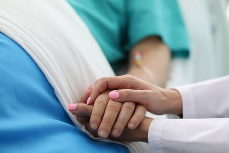 Photo pour Close-up of people holding hands of each other. Woman calming to sick patient in hospital ward. Doc asking about well-being of sick person. Healthcare and medicine concept - image libre de droit