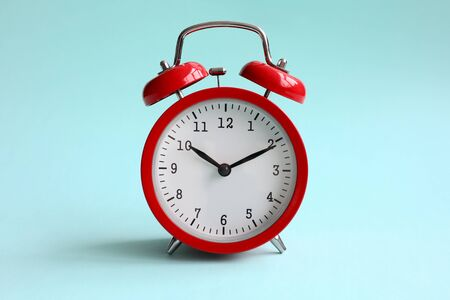 Foto de Red alarm clock on turquoise background shows 10 hours 10 minutes in evening or morning. Time to choice concept - Imagen libre de derechos