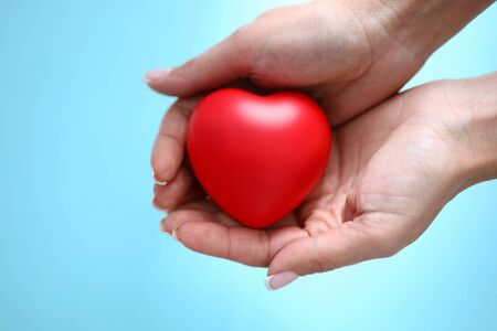 Photo for Woman hand hold red toy heart in hand against blue background closeup. Charity people concept - Royalty Free Image