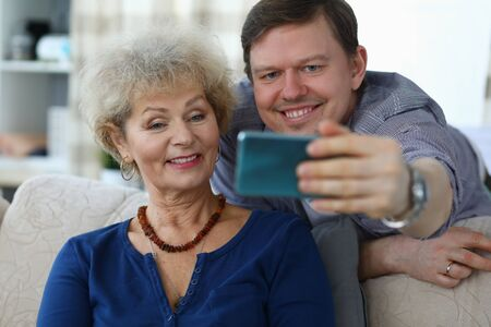 Photo pour Portrait of cheerful mother and son taking selfie to remember. Smiling elderly woman posing for picture on sofa at home. Family relationship and spare time concept - image libre de droit