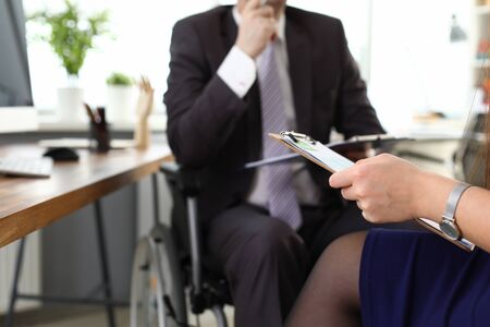Photo pour Male boss on wheelchair speaks with woman in office. Prestigious job for people with disabilities. Man in suit sits in wheelchair. Protection labor rights workers with disabilities - image libre de droit