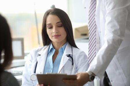 Photo pour Young serious female person staring at list of prescription and listening to her colleague - image libre de droit