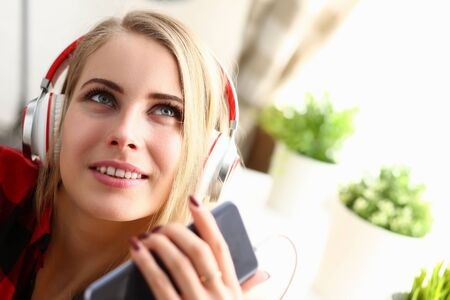 Amazing blonde female person wearing headphones while listening to her favorite song, being at home alone