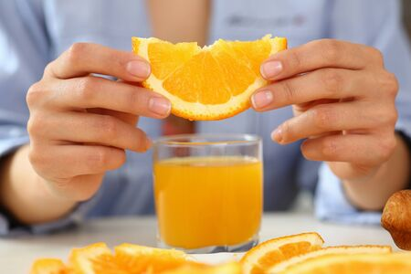 Young female person taking natural vitamins and going to drink orange fresh, sitting in the kitchen