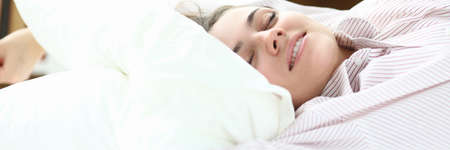 Close-up of smiling woman lying in comfortable bed. Wonderful female person relaxing and enjoying time in bedstead on weekend. Relaxation and vacation concept